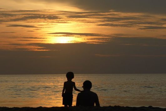 A father and his son enjoying the sunset from Radhanagar Beach